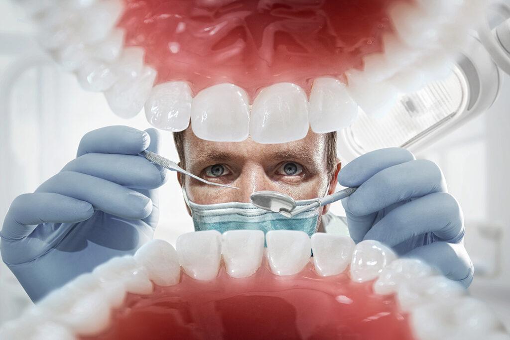 Tandläkare över öppen patients mun som tittar in på tänderna