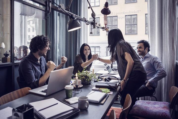 Glada affärskvinnor håller händerna i möte på kreativa kontor