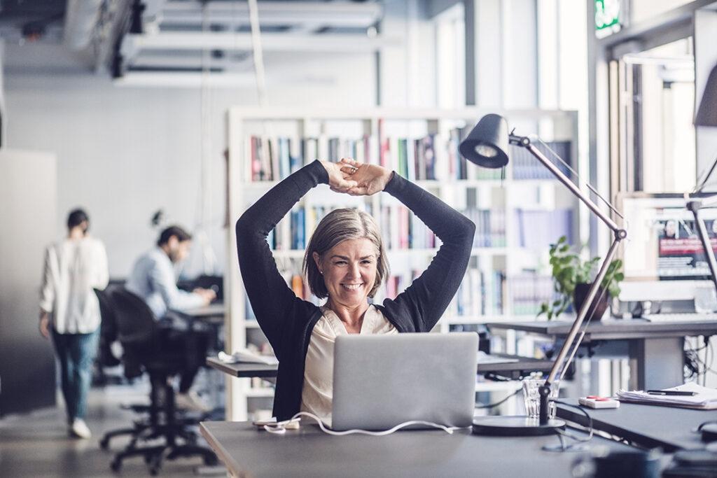 Le affärskvinna tittar på bärbar dator medan du sitter på kontoret